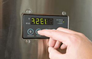 man finger turning down tankless water heater temperature