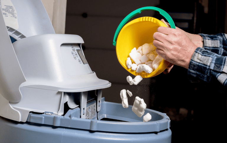 person adds salt to water softener